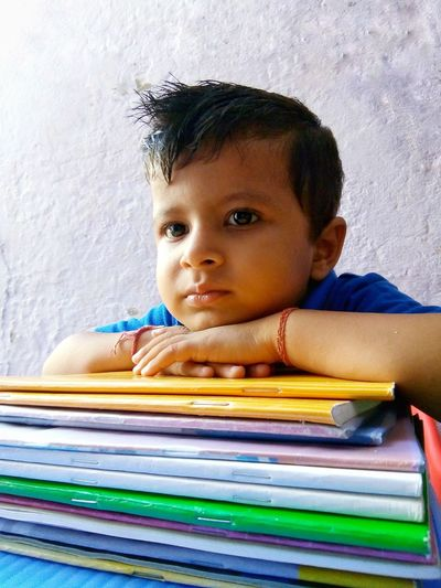 portrait of little boy with books Books Education Knowledge Kid Looking Away Window Light Indoors  Asian  Cute Baby School Work Indian Child Childhood Facial Expression Portrait Thoughtful Thinking Overworked Emotional Stress Over-burdened Tensed Displeased Negative Emotion Pensive Tired