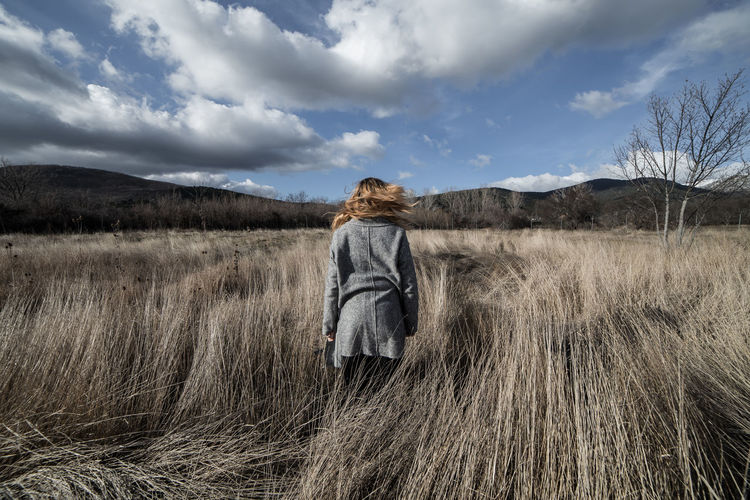 Back view of woman in gray coat standing in autumnal field on background of mountains. Alone Autumn Back View Beautiful Field Freedom Hair Loneliness Meditation Moving Nature Standing Travel Trekking View Woman Adventure Countryside Girl Landscape Meadow Mountains Relaxation Solitude Vacation
