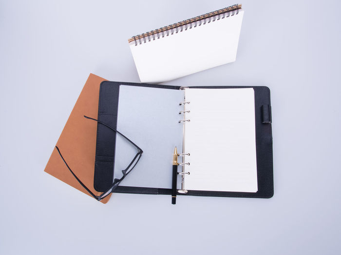 High angle view of books with eyeglasses and pen on white background