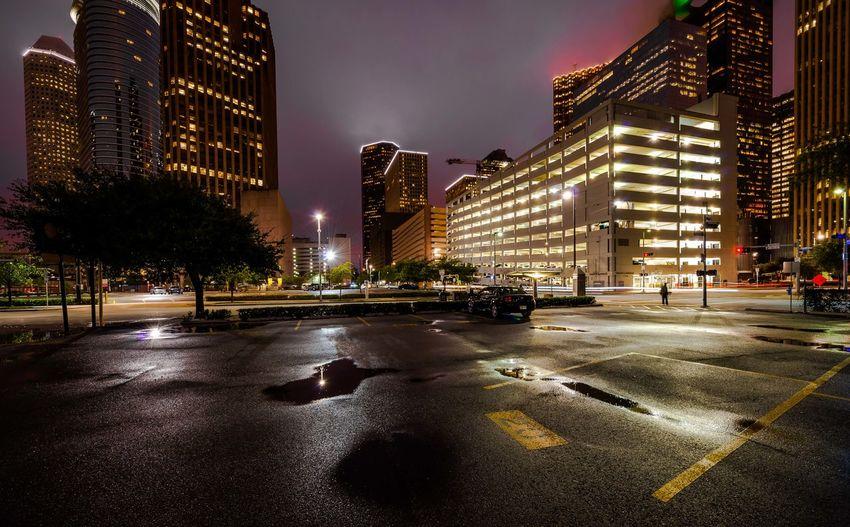 Wet Street Against Illuminated Buildings During Night