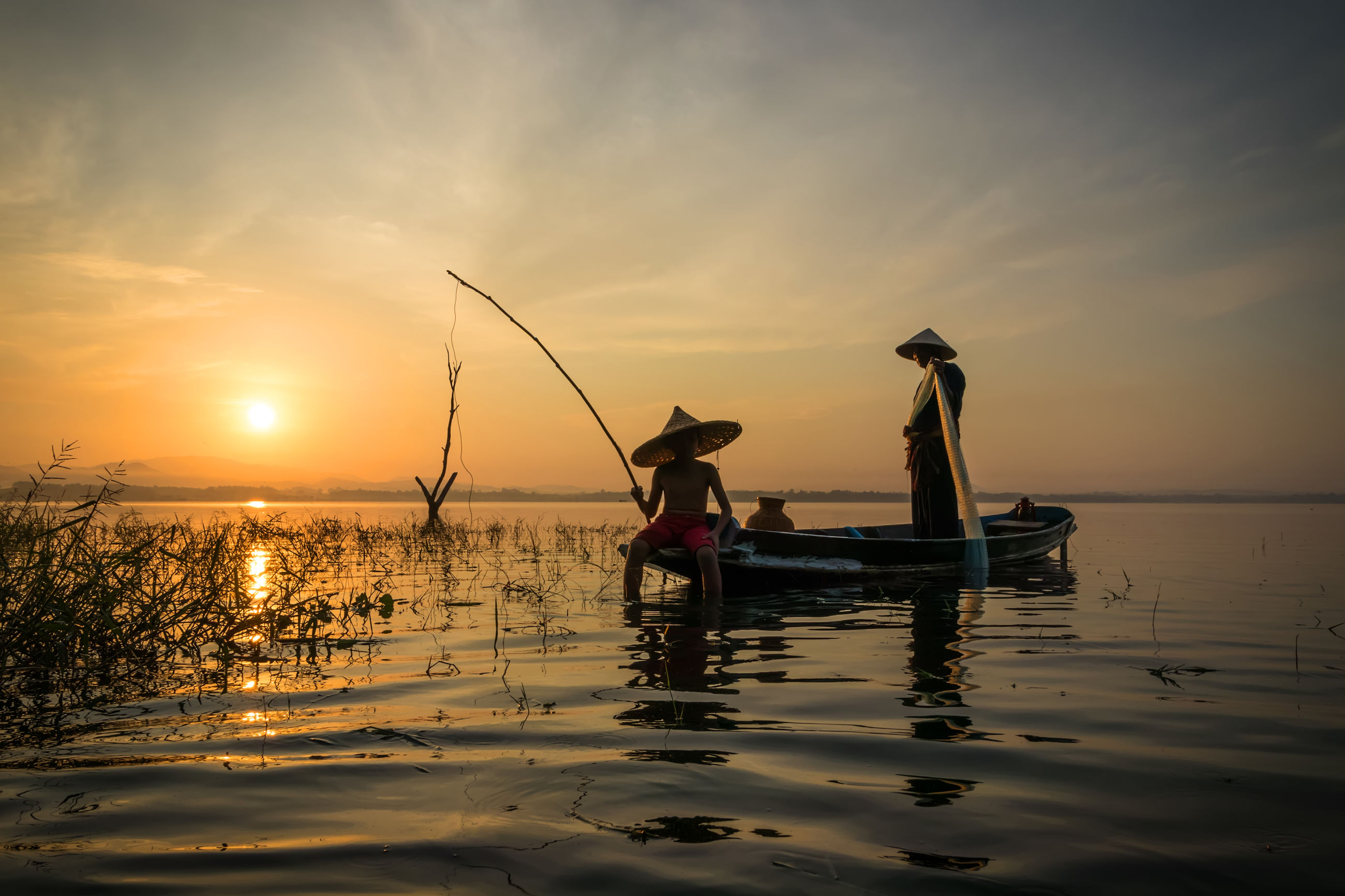 MEN FISHING IN SEA AGAINST SKY AT SUNSET