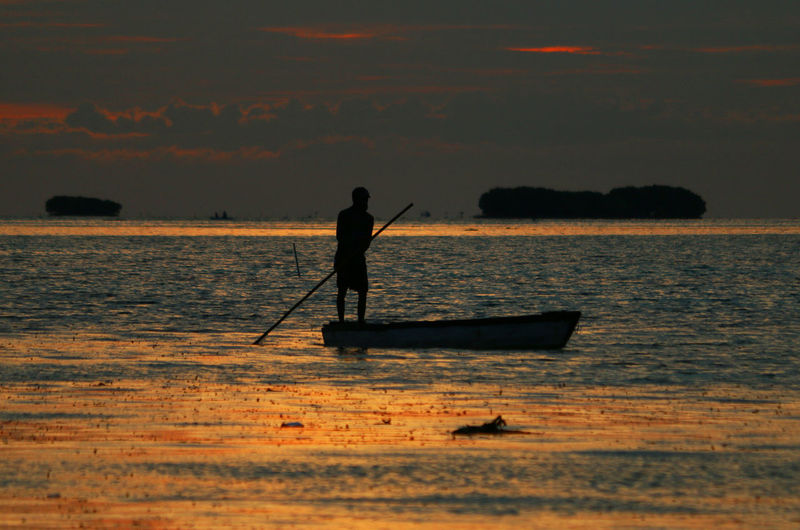 Silhouette Man Rowing Boat On Sea During Sunset