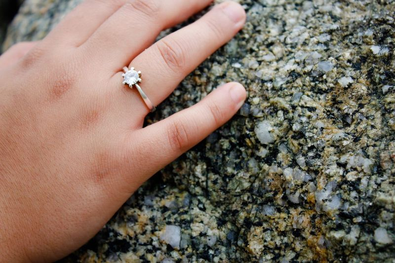 Cropped Hand Of Woman Wearing Ring While Touching Marble