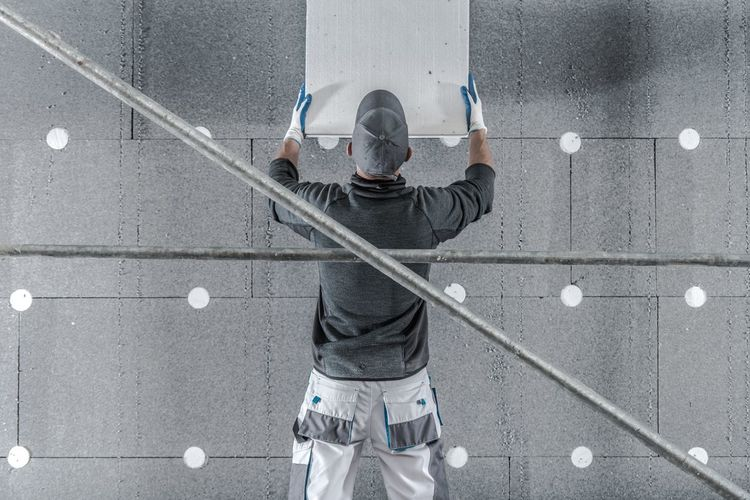 Rear view of manual worker working by wall
