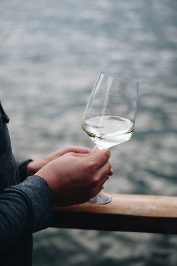 Midsection of man holding wineglass by sea