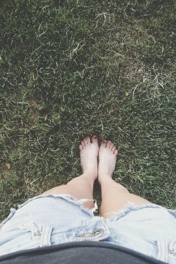 Low section of woman wearing shorts while standing on grass