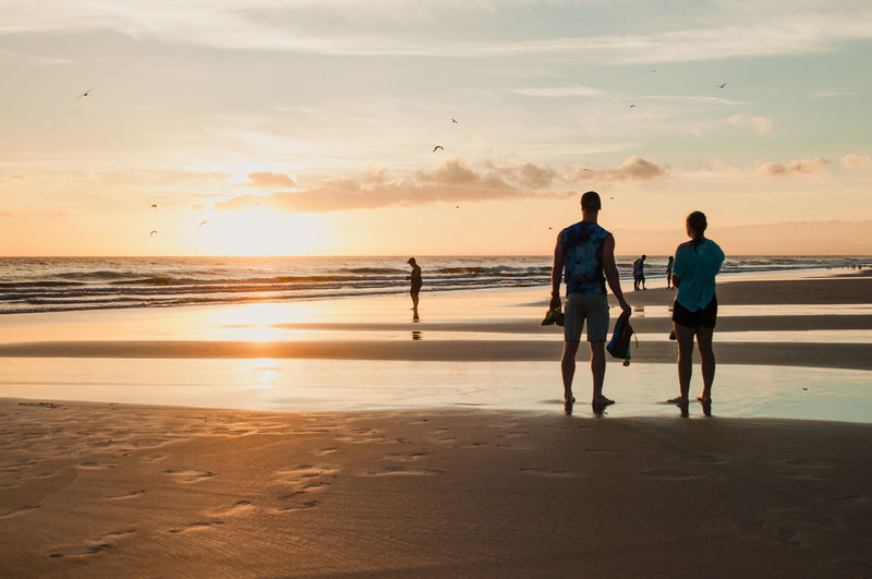 Rear view of men walking on beach against sky during sunset