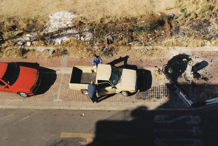 High angle view of people relaxing on footpath