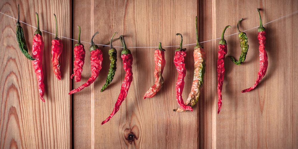 Dried chili peppers hanging by wooden plank