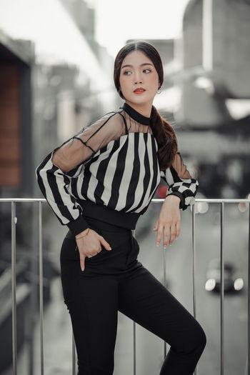 Beautiful woman standing against railing