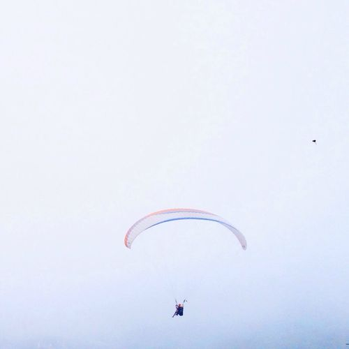 Distant view of people paragliding