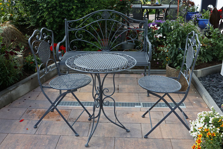 Empty chairs and table by potted plants in yard