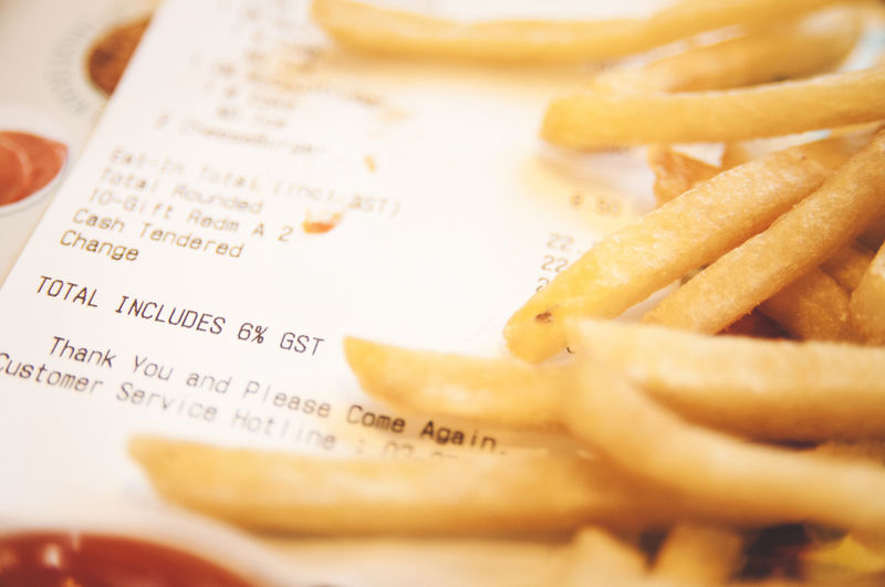 Closeup of french fries with sales receipt showing food tax Diet Fries Shallow Depth Of Field Close-up Fast Food Food French Fries No People Ready-to-eat Sales Receipt Tax Unhealthy