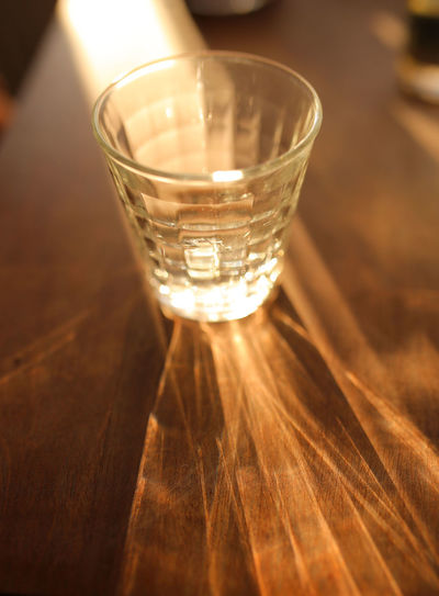 Refraction. Glass Refreshment Drink Table Indoors  Close-up Shot Glass Shadow Focus On Foreground Nightlife Water