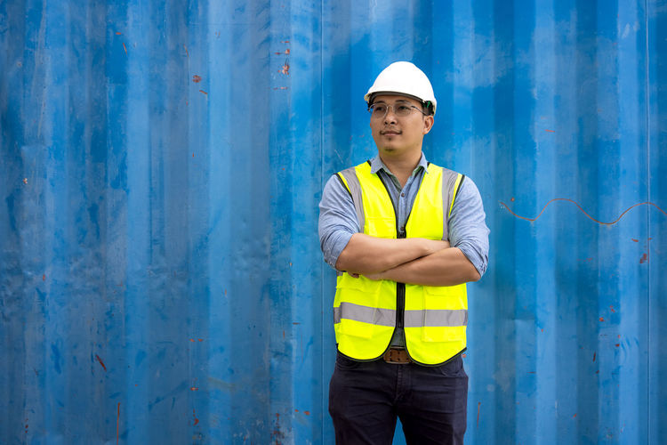 Portrait of engineering man wearing uniform safety suit and helmet in industrial containers.