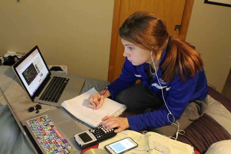 Young woman studying an online college course in the comfort of her room. She has multiple computers to help with information and entering online answers. College Course Modern Workplace Culture Music Plugged In Calculator Computers And Technology Multitasking Online  Studying Studying Hard Young Women