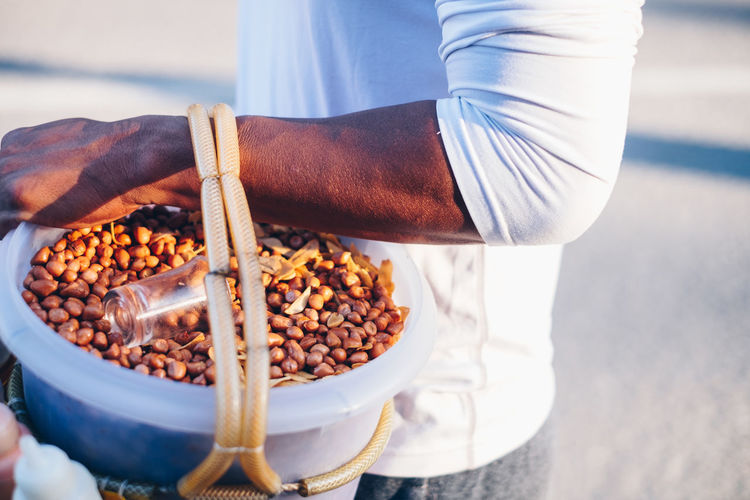Midsection of man holding peanuts in container