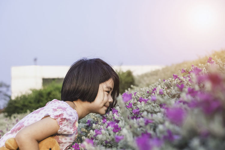 Side view of cute girl smelling flowers against sky