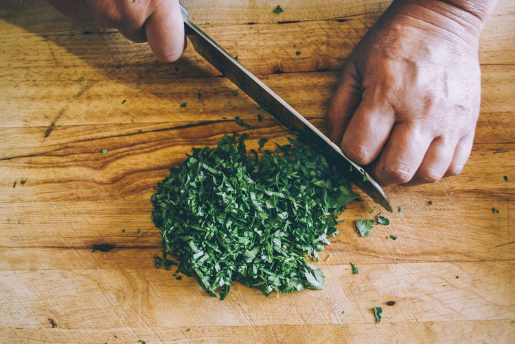 Cropped hand of person cutting cilantro on table