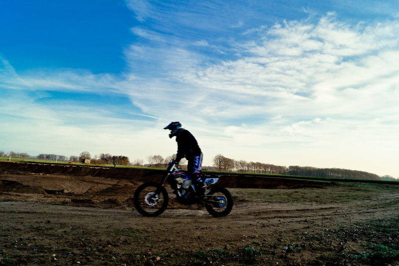 Side view of man performing stunt while riding motorcycle on dirt road against sky
