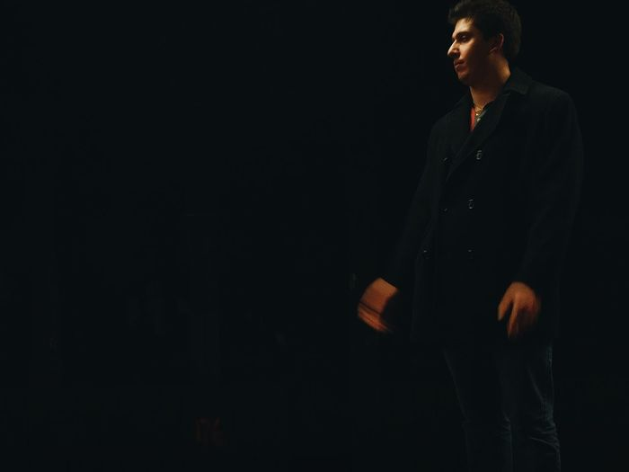 Man standing against black background
