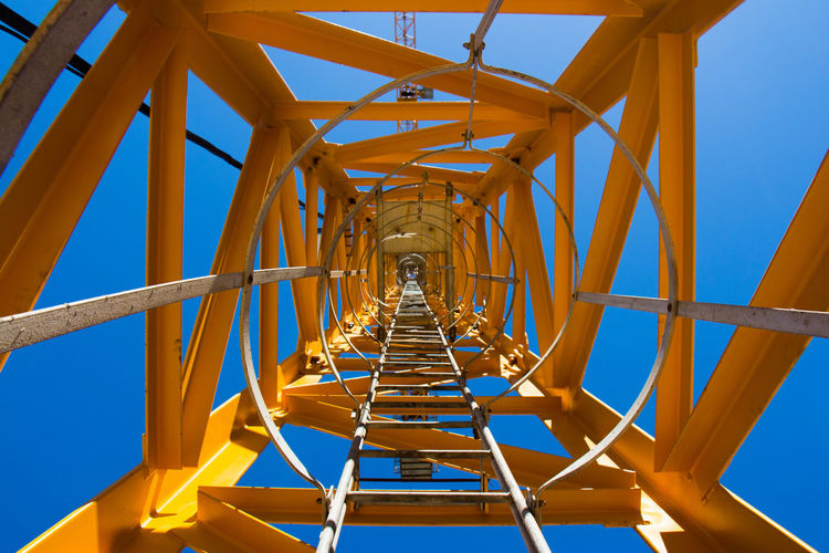 Low angle view of a crane ladder against blue sky