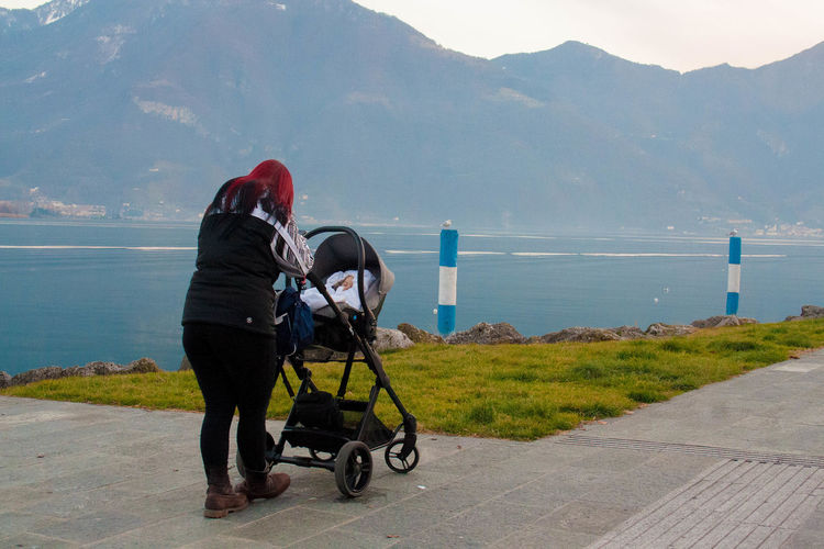 Baby Stroller Beauty In Nature Day Full Length Langbart Lifestyles Lovere Lovere Lake Mom Mountain Mountain Range Nature One Person Outdoors People Real People Rear View Road Scenics Sea Sky Standing Water Women