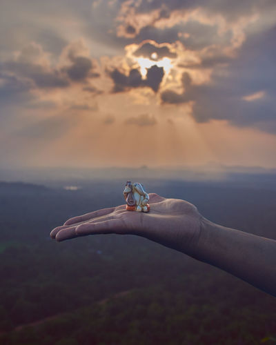 Cropped Hand Of Woman Holding Ganesha Against Sky During Sunset