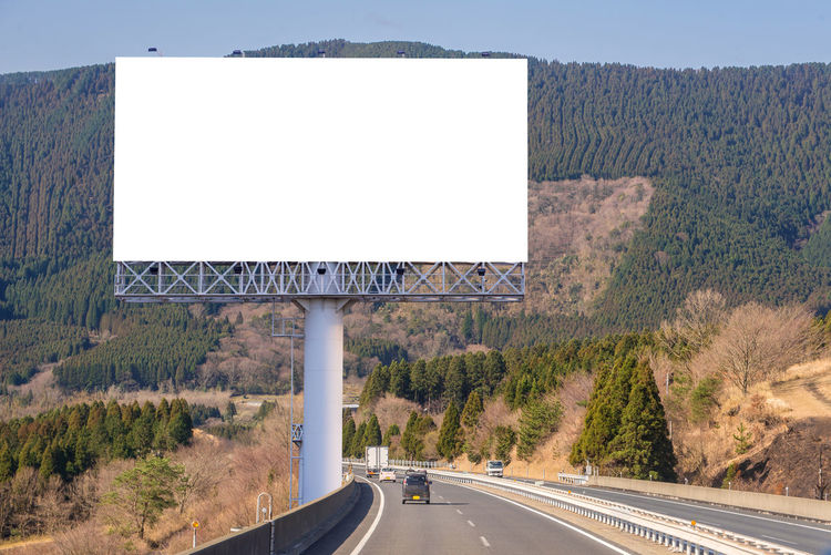 Billboard Blank Clear Sky Crash Barrier Day Direction Empty Highway Marking Mountain Nature No People Outdoors Plant Road Road Marking Road Sign Sign Sky Symbol The Way Forward Transportation Tree