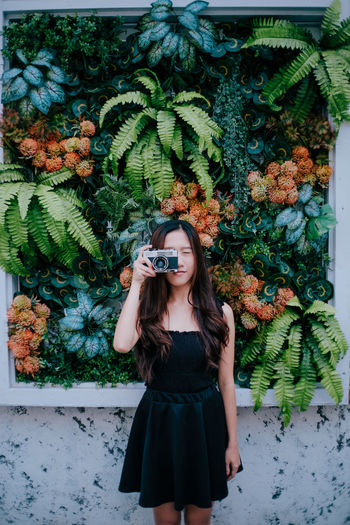 Full length portrait of young woman standing against plants