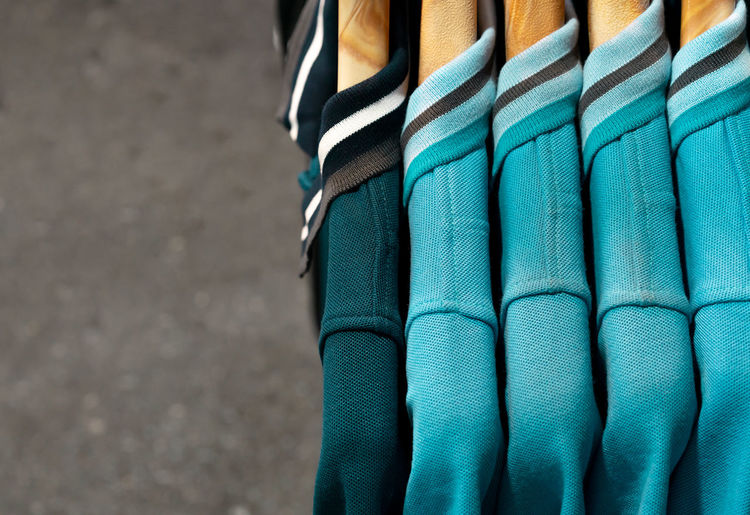 Five green hanging cotton polo shirts - Side view of one dark and four light green teal unisex shirts with collar on wooden hangars Close-up No People Green Color Textile Blue Outdoors Striped Still Life Clothing Rack Shop Store Railing Shirts Polo Shirt  Unisex Fashion Menswear Smart Casual Clothing Informal Short Sleeved Copy Space Wooden Hanger Hanging Collar Market Stall Market Display Plain Plain Colour