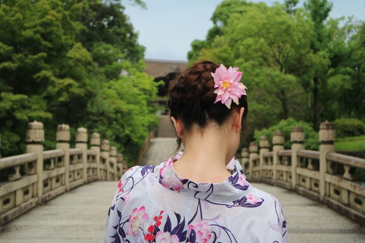Rear view of woman with pink flowers against trees