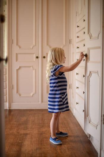 Full length of girl standing against door at home