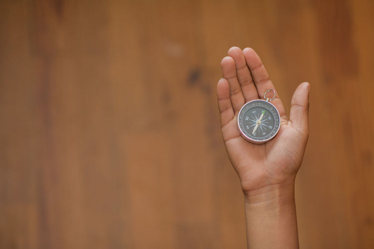 Cropped hand of woman holding navigational compass against wall