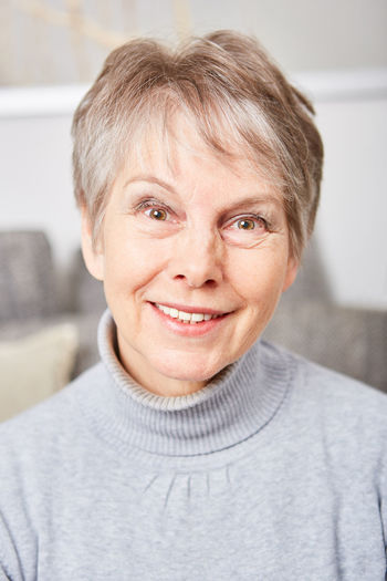 Close-Up Portrait Of Smiling Senior Woman At Home