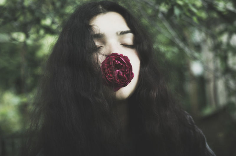Low Angle Close-Up Of Young Woman With Eyes Closed Holding Rose At Park