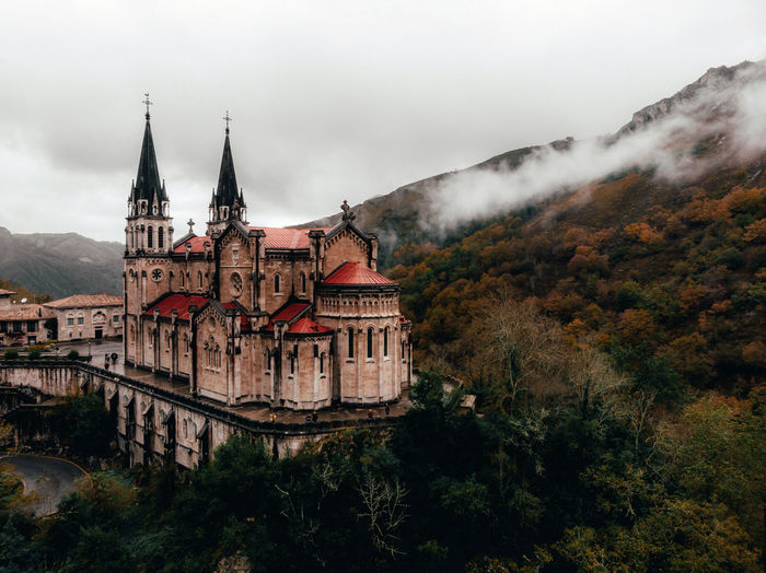 Historic basilica by mountain against cloudy sky