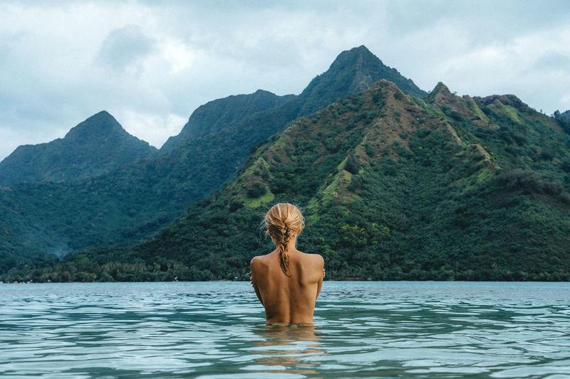 Rear view of shirtless man in water