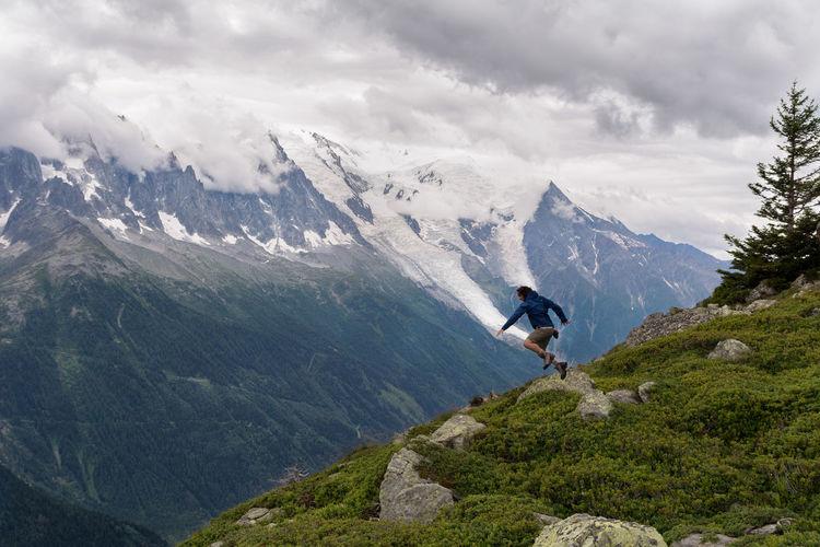 Full Length Of Man Jumping On Mountain Against Sky