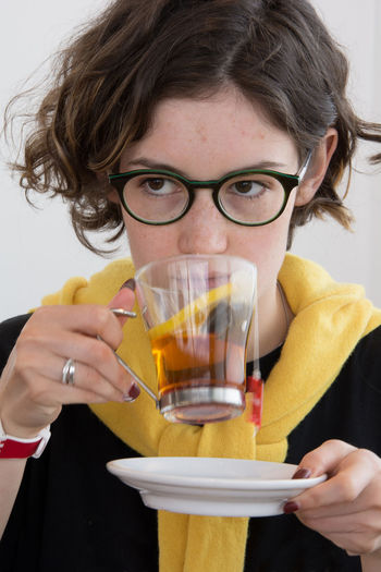 Close-up portrait of a smiling young woman drinking glass