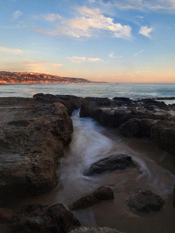 Sunset over the rocks at Shaws Cove in Laguna Beach as water flows over the stone Beach Coast Coastline Laguna Beach, CA No People Ocean Outdoors Scenics Sea Sea And Sky Shaws Cove Sunset Sunsets Wave
