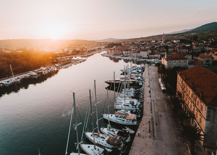High angle view of boats moored at harbor against sky during sunset