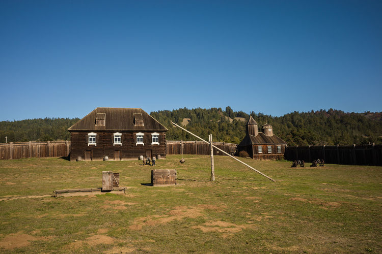 Built structure on field against clear blue sky
