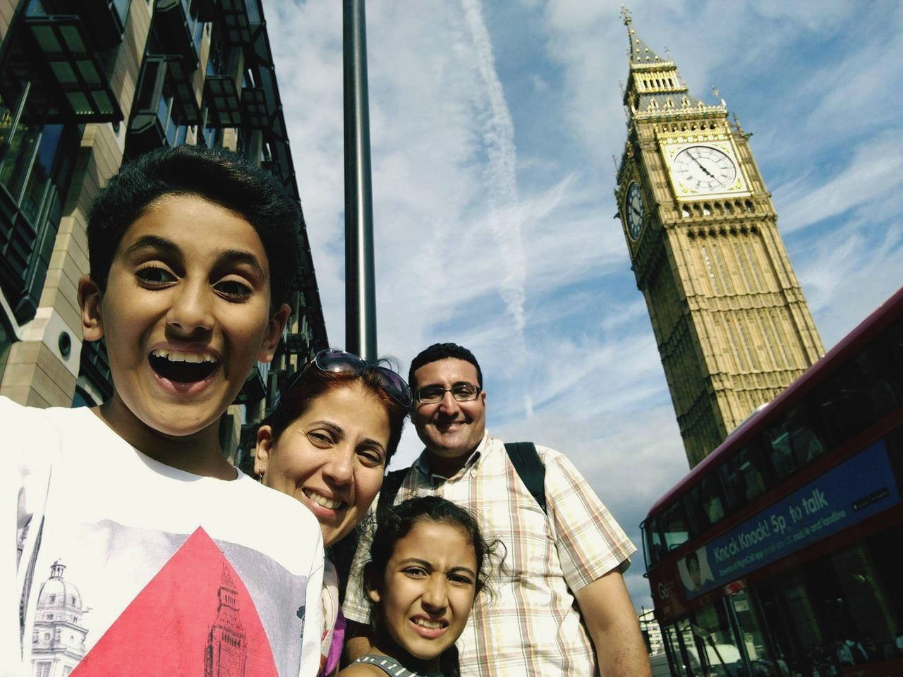 looking at camera, tourism, real people, portrait, smiling, travel, clock tower, architecture, young adult, young women, travel destinations, lifestyles, togetherness, built structure, vacations, leisure activity, building exterior, outdoors, ferris wheel, girls, day, low angle view, headshot, standing, happiness, sky, bonding, selfie, city, people