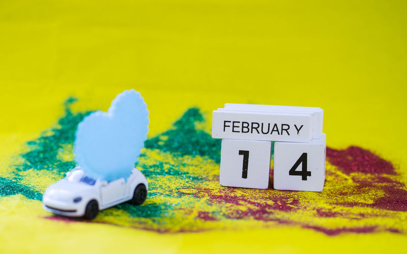 Close-up of calendar and toy car with heart shape on yellow background