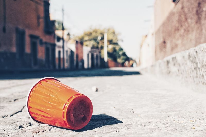 Close-up of disposable cup on street against wall in city