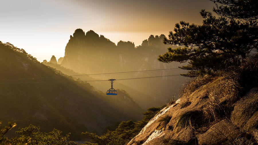 Overhead cable car hanging against mountain during sunset