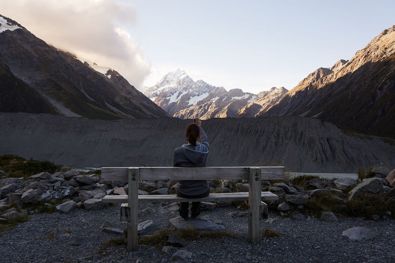 Rear View Of Woman Photographing Mountains While Sitting On Bench Against Cloudy Sky