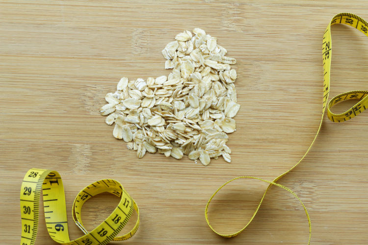 Rolled oat in a shape of heart or love with measuring tape on wooden background Love Heart Heart Shape Measuring Tape Tape Measurement Rolled Oat Oat Health Diet Healthy Healthy Diet Dieting Food Oatmeal Slim Waist Slimming Weight Loss Weightloss Directly Above Wood - Material Wood Grain High Angle View Table Close-up I Love You