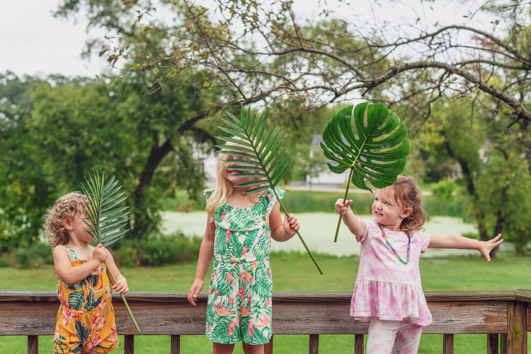 Cute girls holding leaf standing outdoors